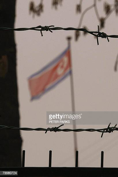 A North Korean flagflutters behind the barbed wire fence of the embassy in Beijing 15 March 2006 as the diplomatic drive to end North Korea's nuclear...