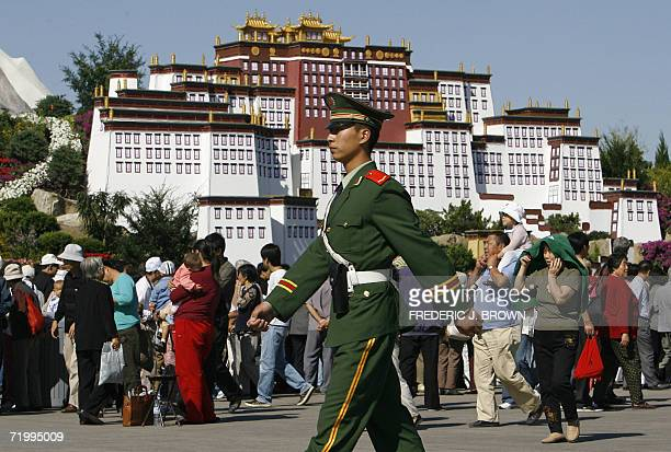 A paramilitary soldier on patrol marches past a crowd gathered in front of a replica of Tibet's most revered landmark Potala Palace 26 September 2006...
