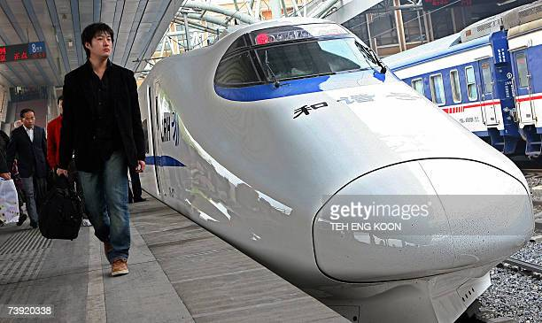 Passenger walks past a China Railway high-speed bullet train, which can run up to 250 kms per hour, at the rail station in central Beijing, 18 April...