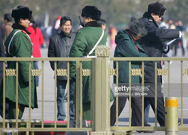 A policeman reads a woman's petition while leading her away to be escorted off Tiananmen Square amid tightened security in Beijing 06 March 2007...