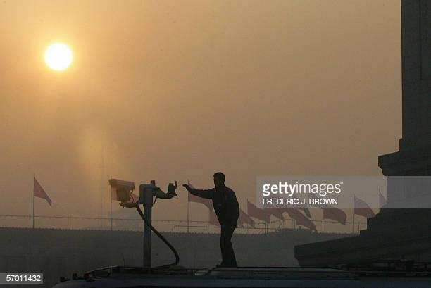 A security camera is set up at sunrise overlooking Tiananmen Square amid tight security for the opening session of the National People's Congress in...