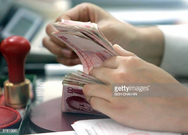 A stack of hundred yuan notes is counted at a local bank in Beijing 15 May 2006 China set its currency the yuan at 79982 to the US dollar early 15...