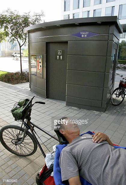 A vendor takes a nap beside a public bombproof toilet in Beijing's Zhongguancun Silicon Valley area 06 September 2006 It was reported 06 September...