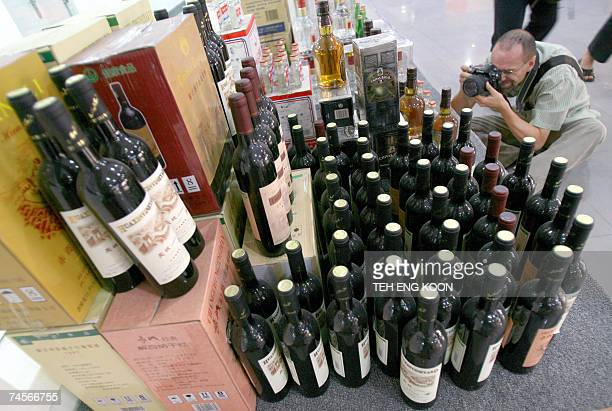 A visitor takes a picture of counterfeit wine bottles at the Beijing administration for industry and commerce center for food safety test in Beijing...