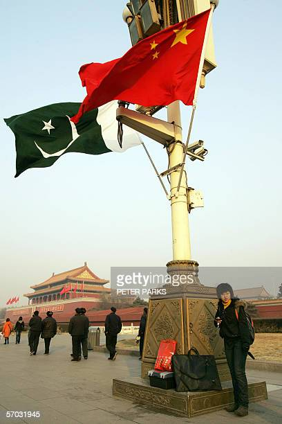 A woman stands under Pakistani and Chinese flags at Tiananmen Gate on view for Pakistan President Pervez Musharraf's visit to the Chinese capital...