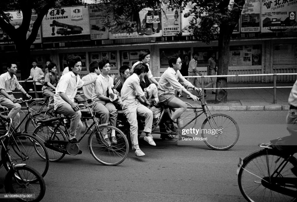 Group of men with injured women on cycle (B&W) : News Photo