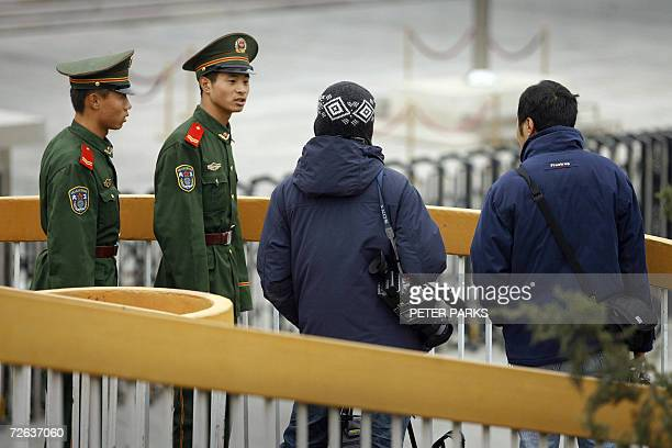 Chinese paramilitary police question two Hong Kong journalists outside Beijing's High Court before the hearing of Ching Cheong a Hong Kongbased China...