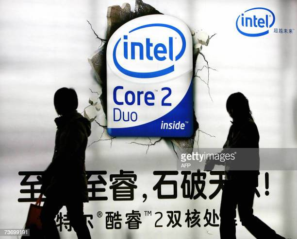 Chinese shoppers walk past an advertising billboard of the US chip giant Intel on display at a shopping mall in Beijing, 26 March 2007. US chip giant...