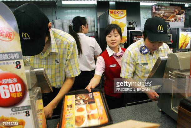 Chinese workers go about their business behind the counter at a branch of US fastood giant McDonalds in Beijing 02 April 2007 Chinese labour...