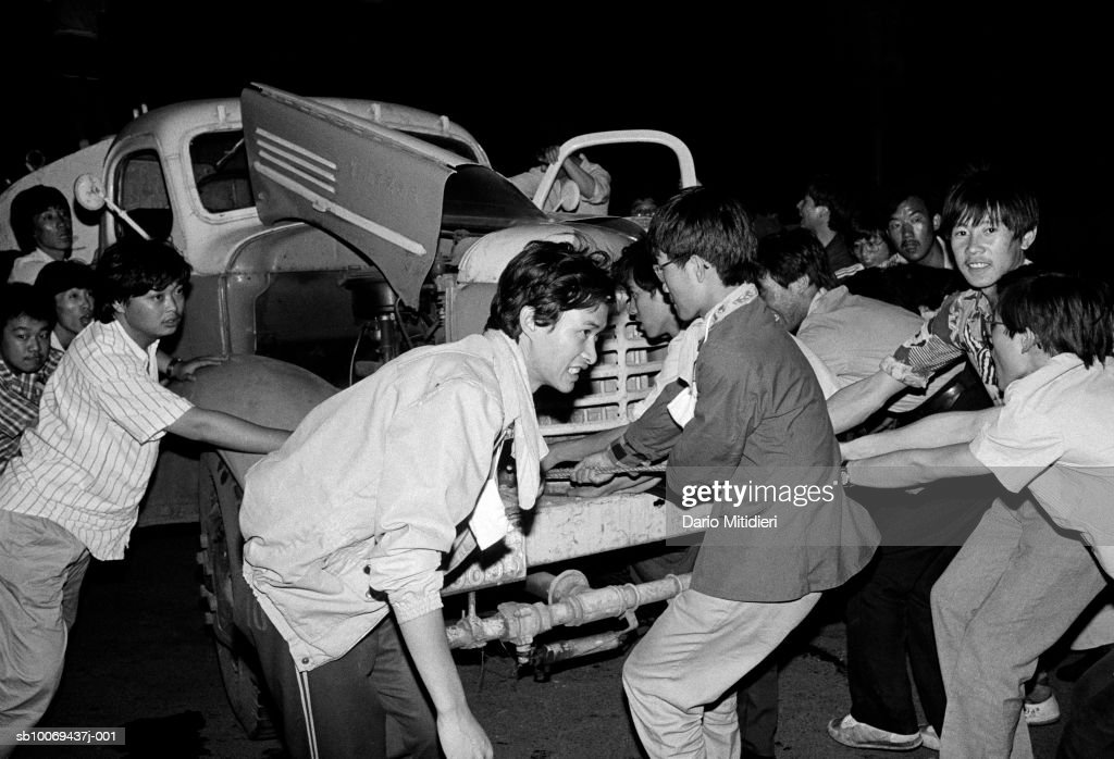1989, Beijing, China, Democratic protesters drag a wrecked truck to form a barricade against the Chinese army entering Tiananmen Square in Beijing in June 1989.; date created: 2008:05:07; Tiananmen Square Massacre