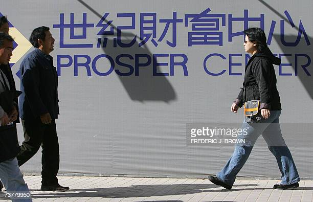 Pedestrians walk past the board of a building on which name of the building under construction is displayed in Beijing's Central Business District 03...