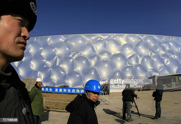Security guards man their positions as a foreign television crew films the exterior of the National Swim Center or 'Water Cube' being built for...