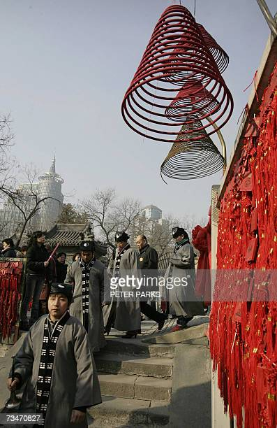 Taoist monks walk under incense coils at the Dongyue Miao Taoist Temple on on the second day of the Lunar New Year holiday 19 February 2007 Lunar New...