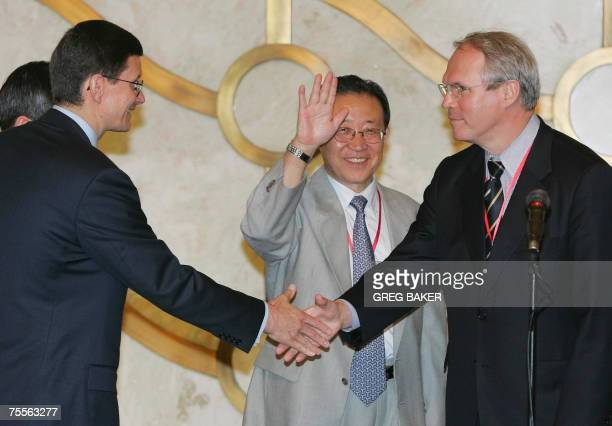 US Assistant Secretary of State Christopher Hill shakes hands with Russian Ministry of Foreign Affairs Ambassador Vladimir Rakhmanin as North Korean...