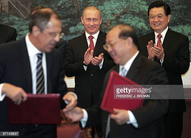 Visiting Russian President Vladimir Putin and Chinese President Hu Jintao applaud as respective government officials exchange documents during a...