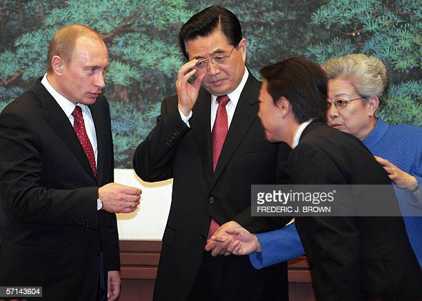 Visiting Russian President Vladimir Putin speaks to a translator as Chinese President Hu Jintao adjusts his glasses and State Councillor Wu Yi...