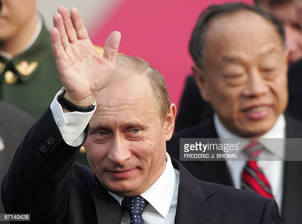 Visiting Russian President Vladimir Putin waves on arrival at the airport in Beijing 21 March 2006 followed by Chinese Foreign Minister Li Zhaoxing...