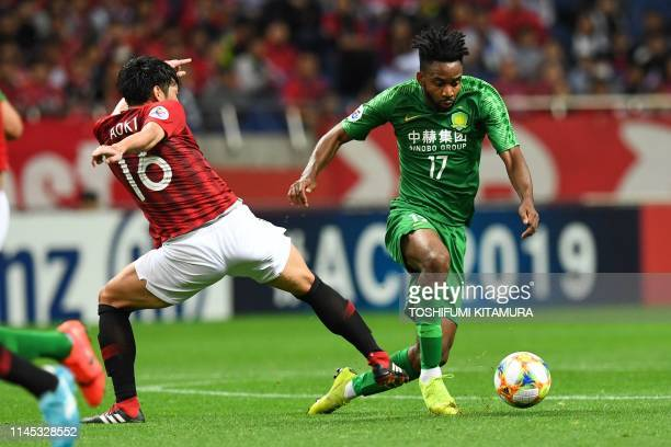 Beijing Guoan's Cedric Bakambu fights for the ball with Urawa Reds' Takuya Aoki during the AFC Champions League group G football match between...