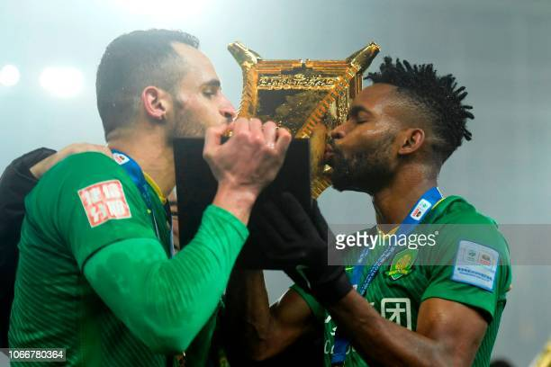 Beijing Guoan's Renato Augusto and Cedric Bakambo kiss the trophy after winning the Chinese FA Cup final after drawing 22 in the second leg with...