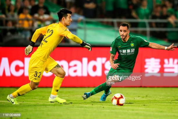 Beijing Guoan's Renato Augusto fights for the ball with Guangzhou Evergrande's goal keeper Liu Dianzuo during their Chinese Super League football...