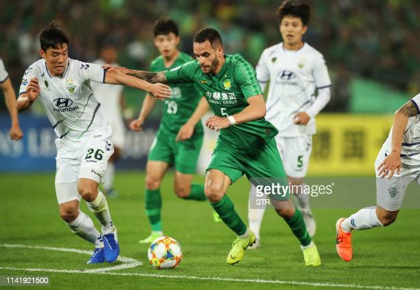 Beijing Guoan's Renato Augusto fights for the ball with Jeonbuk Hyundai Motors Hong JeongHo during the AFC Champions League group stage football...