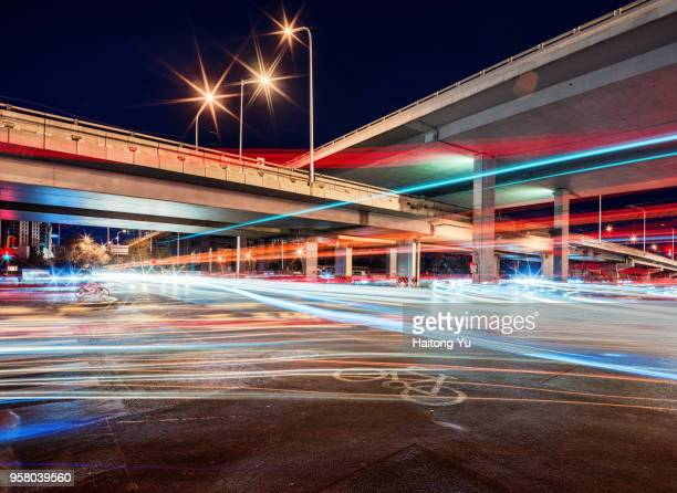 Beijing. Light trails under a viaduct at night.