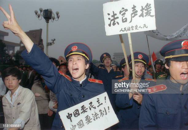 Beijing magistrates wearing court uniforms join workers demonstrating in Beijing streets 18 May 1989 in support of student hunger strikers gathered...