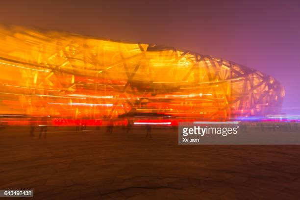 beijing olympic stadium know as bird nest at night with lights on - stadio olimpico nazionale foto e immagini stock