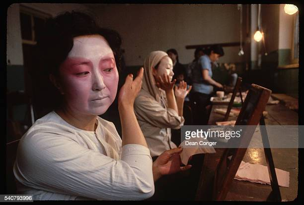 A Beijing Opera singer applies her stage makeup for a performance of Stopping the Horse Beijing China