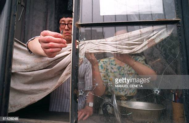 Beijing resident on the west side of Tiananmen Square shows a slug from the automatic rifle fired by the army 04 July 1989 that went through his...
