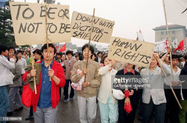 Beijing residents holding placards written in english walk in procession on May 18, 1989 in support to student hunger strikers who entered the 6th...