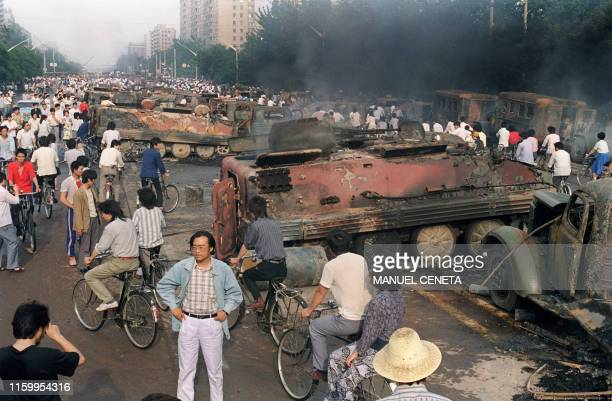 Beijing residents inspect the interior of one of over 20 armoured personnel carrier burnt by demonstrators to prevent the troops from moving into...