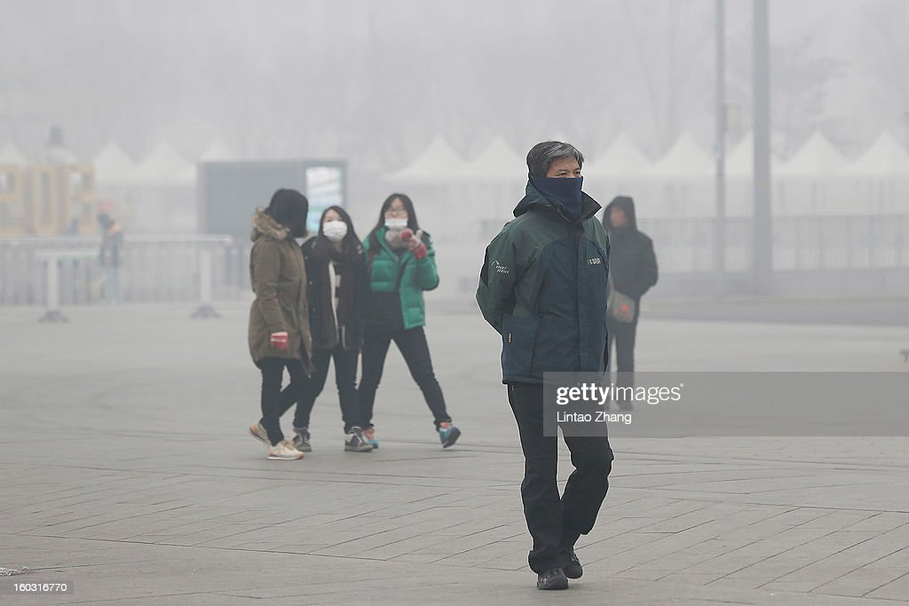 Beijing residents wearing masks walk through fog as severe pollution continues to affect the capital on January 29, 2013 in Beijing, China. China's ruling Communist party has announced temporary emergency measures in an attempt to combat the current hazardous levels of pollution enveloping Beijing.
