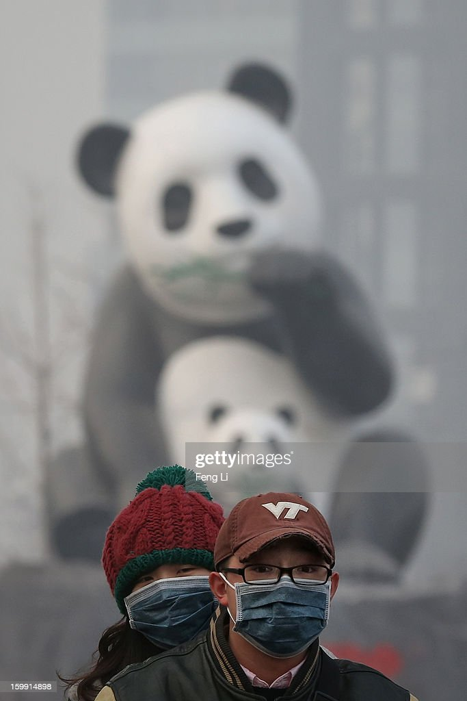 Beijing residents wearing the masks ride a motorcycle through a panda sculpture during severe pollution on January 23, 2013 in Beijing, China. The air quality in Beijing on Wednesday hit serious levels again, as smog blanketed the city.