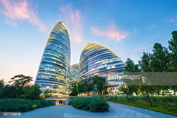 beijing wangjing soho at dusk - beijing stock pictures, royalty-free photos & images