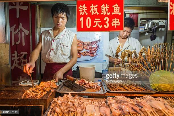 Beijing jeune homme cuisiner des délices locaux au marché de nuit en Chine