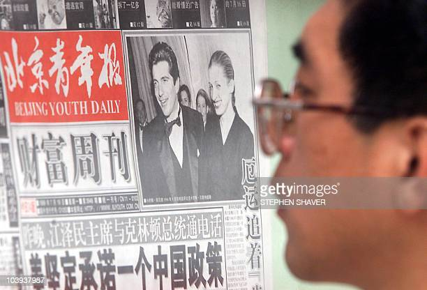 A Beijinger reads a local newspaper headline story 20 July 1999 on a sidewalk in downtown Beijing of the tragic death of John F Kennedy Jr and his...