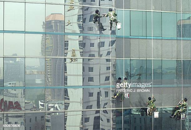 Beijing's urban growth is reflected on the glass exterior of a building15 April 2004 as window cleaners make their descent to clean China's economy...