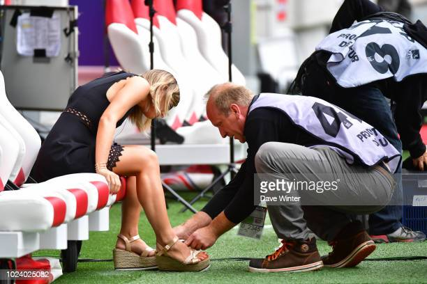 BeIN Sport tv presenter Margot Dumont has some repairs done on her shoes during the Ligue 1 match between Lille and Guingamp on August 26, 2018 in...