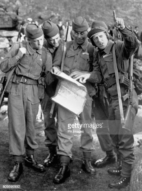 Being briefed on Dartmoor is discjockey Jimmy Savile right during a 30 mile forced march attempt with the Royal Marines just to see how tough he can...