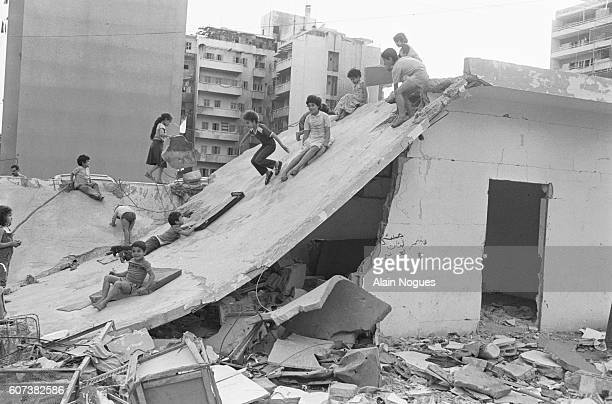 Beirut children play and slide on the roof a collapsed house. The ruins testify to the intense fighting going on in the city since June 1982 as a...