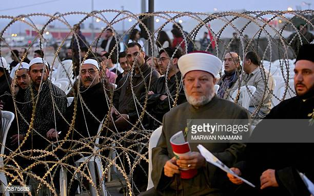 Barbed wire splits Lebanese Christian, Muslim and Druze clerics as they attend a ceremony to mark the 32nd anniversary of Lebanon's 1975-1990 civil...