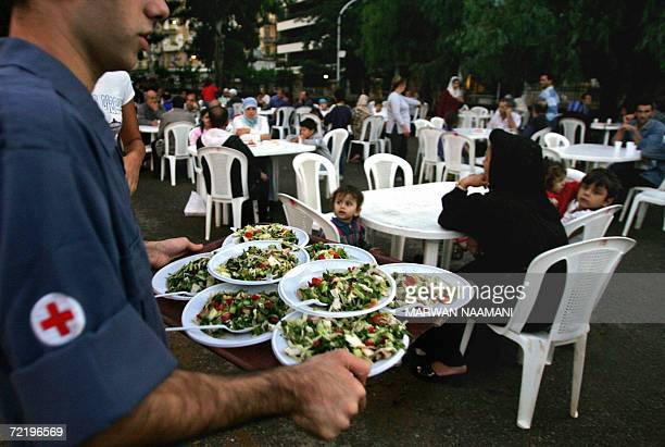 A Lebanese Red Cross volunteer serves food for Muslims to break their fast at a public garden in Beirut 17 October 2006 Scores of needy Lebanese...