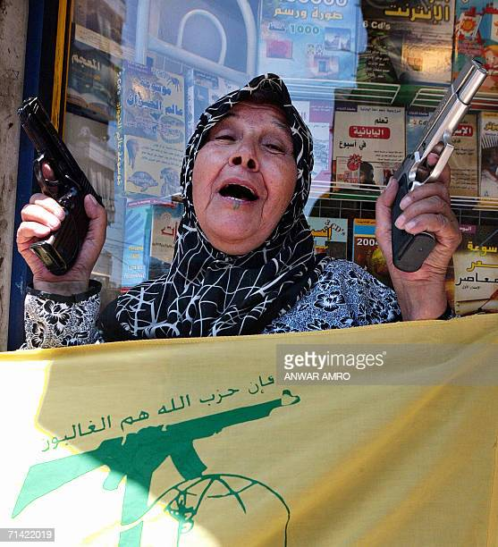 A Lebanese woman brandishing guns jubilates in Beirut's southern suburbs after proIranian Hezbollah fighters captured two Israeli soldiers in south...
