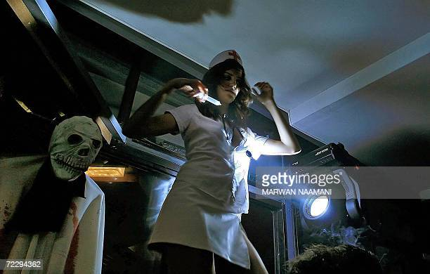A Lebanese woman dressed as a nurse dances on the bar of a night club in Beirut in the early hours of 29 October 2006 to celebrate Halloween A...