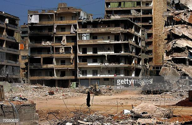 A Lebanese woman walks in front of destroyed buildings in the devastated southern suburb of Beirut 28 September 2006 The Lebanese government is...
