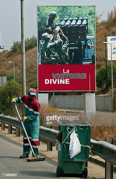 A Lebanese worker cleans 21 August 2006 a Beirut highway in front of a poster erected by zealots of proIranian Hezbollah showing an image of fighters...