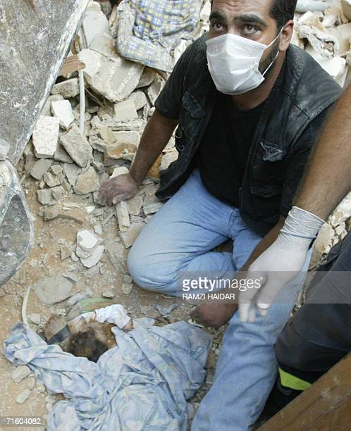 A rescue worker sits near the dead body of ten dayold Lebanese baby Waad liying in her mother's arms 08 August 2006 found in the rubble of a building...