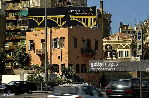 Cars speed past a building bearing a Johnnie Walker whiskey advertisement with a twist on their classic advertising campagin Keep Walking in downtown...