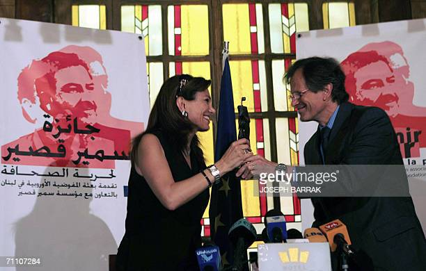 Journalist Gisele Khoury accepts an award from EU ammbassador to Lebanon Patrick Renauld 02 June 2006 during a ceremoney to present the first...